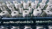 szövés : Many spools with fiber spinning on a factory machine in a facility. Textile factory equipment in work.