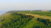 парашют : One person flying with a glider over green trees. Paragliding, action, extreme sport concept.