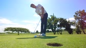 sofőr : Man gets a ball into a hole, while playing golf. Stock mozgókép