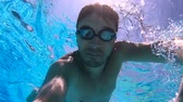 plavec : A person swims in a pool, wearing goggles, slow motion.