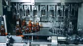 koňak : Factory machine is pouring alcohol into empty bottles