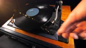 sztereó : A man moves away a needle from a vinyl disk and takes it.