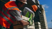 propriedade : Male workers are brushing a newly-built brick wall