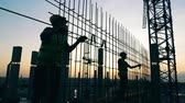 carcasse : Construction workers are making a metal framework at sunset Vidéos Libres De Droits