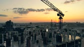 keretében : High-rise building in progress with cranes at sunset