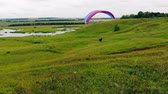 fallschirm : Massive field with the paraglider running up and flying. Extreme sport concept.