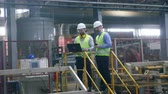 workforce : Two engineers check working machines at a brick factory. Stock Footage