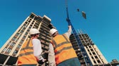 high rise buildings : Two engineers are observing construction of multistory buildings