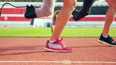 struggle : Close up of healthy and prosthetic legs while running