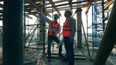 felügyelet : Male engineers are planning constructions among the scaffolding
