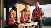 felügyelet : Team of building workers are discussing layouts