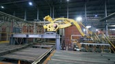consignment : Modern factory machine moves bricks from a conveyor in a facility.