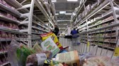 cartn corrugado : 03232016 Minsk, Belarus, hypermarket Euroopt: Buying products in the hypermarket. Buying meat, eggs and products. The man rolls the cart with food