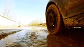 go cart : Cars wheels in mud in the forest, off-road. Driving at country road. View from outside car cabin. POV. Machine goes on the road. Stock Footage