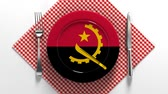 utensili da cucina : National cuisine and dishes of Angola. Delicious recipes from Europe. Flag on a plate with food from Angola. Filmati Stock