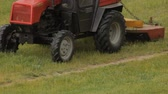 arando : Old tractor mows the grass on the field