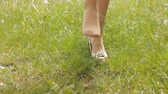 excitação : A girl in nature takes off her shoes, close-up, grass