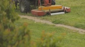 tinted : Tractor mows the grass in the rain, close-up