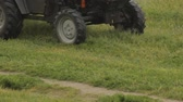 arando : Tractor mows the grass in the rain, close-up
