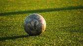 goleiro : shabby soccer ball lies on the football field, close up