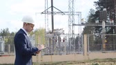 eletricista : A young engineer in the background of a power plant writes data to a tablet