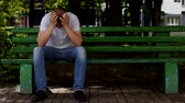 annoyance : A young man sits on a bench with his head down and holds his head, problem Stock Footage