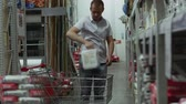 cartilla : buyer takes the goods from the shelf and puts them into the shopping cart Archivo de Video