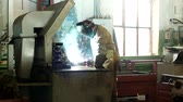 titular : Working welder at the factory in a protective suit welds the part, the welder makes the part, the production, welding