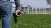 угроза : man with a gun in his hand is on the playground, kids at risk Стоковые видеозаписи
