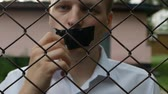 imprison : The man behind the bars is unfastened from the mouth of the tape and says the phrase, violation of the law on disclosure, close-up, slow motion Stock Footage