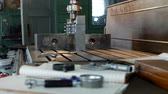 dimensões : A private workshop for working with metal parts, in the background a drilling machine drills a hole in the pulley, on the table lie measuring instruments, mensuration