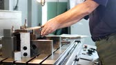 artisan : A man specializes in a driller prepares a metal workpiece for further drilling and machining on a drilling machine, a private workshop, handiwork Stock Footage