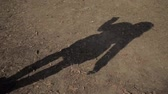восхождение : The shadow on the ground of a girl walking along the road, slow-mo, girls shadow