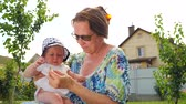 timeless : Toddler with flower on grandmothers hands. Young grandmother with baby. Stock Footage