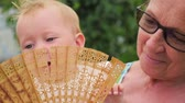timeless : Woman and child. Older and younger. Beautiful ladies. Toddler playing with fan on grandmothers hands.