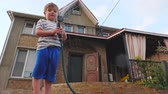 шланг : Private house in the summer. Small business concept. Boy in the backyard of a country house in the summer relax playing with water hose. Стоковые видеозаписи