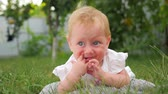 teething : Active baby background. Toddler teething problems. Baby girl lying on green grass. Front garden background. Stock Footage