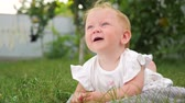 teething : Baby teething background. Baby teething problems. Baby lying on green grass. Kid playing in the garden. Teeth are cutting through. Blue eyed girl smiling outdoor. Child in summer forest. Eco living.