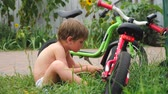 saddle : Boy fixing bicycle. Front, back yard background. Transport and children. Cycle on the grass. Happy childhood concept. Boy playing outside. Summer holidays background. Repair of bicycles background.