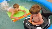 developing : Children and nature. Summer time. Traveling concept. Vacation. Travel with children. Water games. Happy childhood concept. Cheerful children playing in water. Water pool on front, back yard. Stock Footage