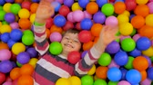 método : Entertainment concept. Modern lifesyle background. Boy lying in the pool with colorful soft balls Waving hello to everybody Top view. Happy childhood concept. Happiness in bright colors.