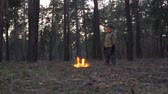 zvěř a rostlinstvo : Fire starts in the forest. Arson in Park. Setting fire to nature, flora, fauna. Boy looking around while standing in front of fire-raising in the forest, park. Treating the fire as arson.