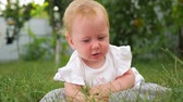 dor de dente : Baby girl on fresh air. Montessori concept. Brain development. Baby development background. Children and nature. Baby sunbathing on green grass on front, back yard.
