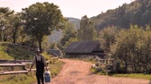 ukrajinec : A man with a portable walkway in a mountain village. Road in sunny summer day. With suitcase on summer day