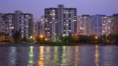 povero : Complex of appartment buildings in the evening city near the large lake, with street lights reflecting in the water. Buildings in twilight near lake. Buildings and lights in appartments evening. Filmati Stock