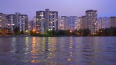 郊外の : A complex of appartment buildings in the evening city near the large lake, with street lights reflecting in the water. Buildings in twilight near lake. Buildings and lights in appartments evening. 動画素材
