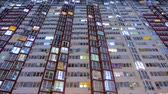 fogyasztás : Light in the windows of housings. Turns on and off the light in the windows of houses. Lights of the night city. Time lapse. Business center outdoor. Stock mozgókép