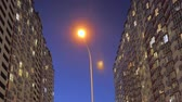 郊外の : Nighttime time lapse of illuminated building windows at night with people living in flats with balcony. Electricity consumption concept. View from below. City street in evening