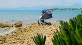 non urban scene : Baby vehicle near sea water in Greece. Healthy air near the sea for baby. Toddler transport with seascape on background. Baby stroller on seashore. Baby sleeping in stroller at seaside