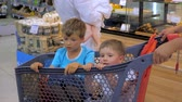ATHENS, GREECE - JULY 10 2019: Father driving sons in shopping cart along the supermarket. Father with cute little sons going with shopping cart with small boys sitting in it. Buying food and drink.